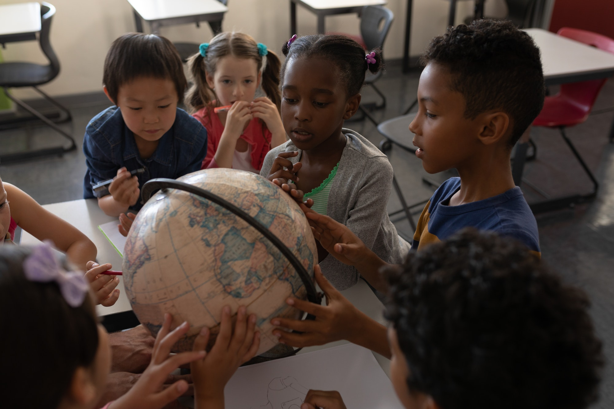 Group of kids studying a globe together in classroom